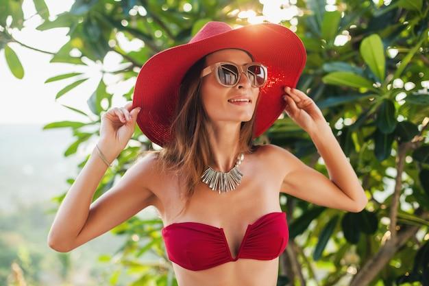 Junge frau mit schönem schlanken körper, der roten bikini-badeanzug, strohhut und sonnenbrille trägt, die auf tropischem villenresort im urlaub auf bali, dünne figur, sommerart-trendzubehör, sonnig entspannen