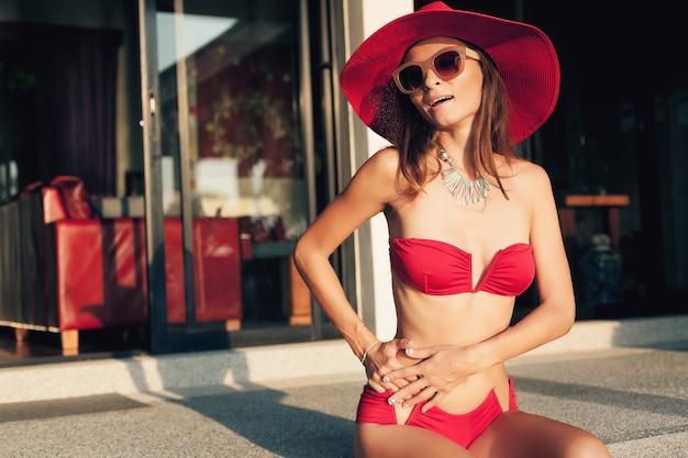 Junge frau mit schönem schlanken körper, der roten bikini-badeanzug, strohhut und sonnenbrille trägt, die auf tropischem villenresort während des urlaubs in asien, dünne figur, sommerart-trendzubehör entspannen