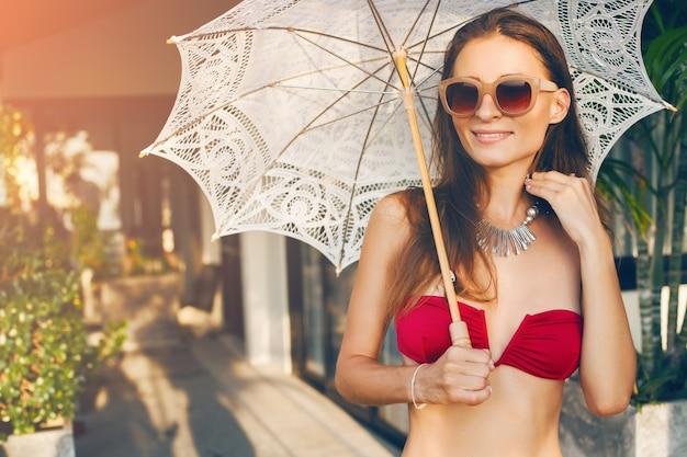 Junge frau mit schönem schlanken körper, der roten bikini-badeanzug trägt, der spitzen-sonnenschirm auf tropischem villenresort während der urlaubsreise in asien, dünne figur, sommerart-trendzubehör hält
