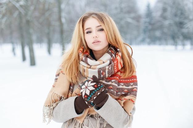 Junge frau mit schönen augen mit blassrosa lippen mit einem stilvollen vintage-schal in einem warmen mantel mit gestrickten handschuhen, die aufwerfen