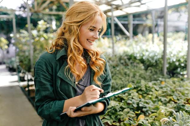 Junge frau mit schönen blonden haaren und sanftem lächeln, gekleidet in grünes gewand mit gürtel, arbeitet im gewächshaus