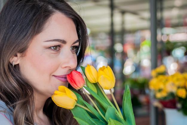 Junge frau mit schönen bouquet von tulpen auf blumenladen hintergrund. porträt einer hübschen frau lächelnd beim halten frische tulpen.