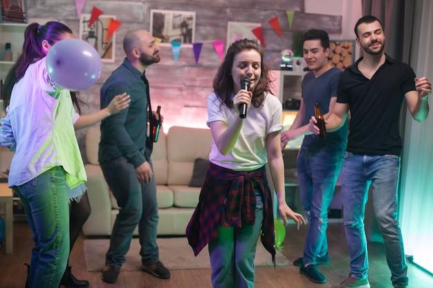 Junge frau mit schöner stimme, die für ihre freunde auf der party singt. karaoke-unterhaltung.