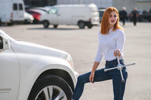 Junge frau mit schraubenschlüssel wartet auf hilfe beim radwechsel an einem kaputten auto