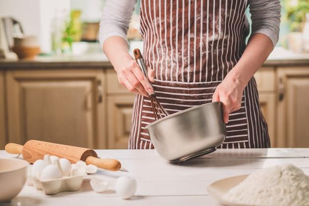 Junge frau mit schüssel mit teig und schneebesen, nahaufnahme. eine frau in gestreifter schürze kocht in der küche