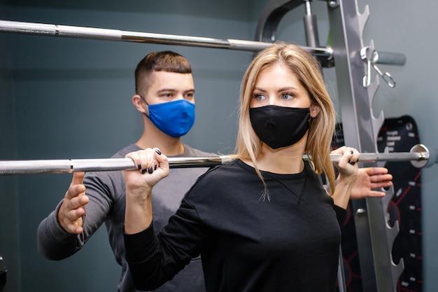 Junge frau mit schutzmaske, die mit personal trainer im fitnessstudio während der covid-19-pandemie trainiert. sie pumpt ihre muskulatur mit einer hantel auf. weicher fokus