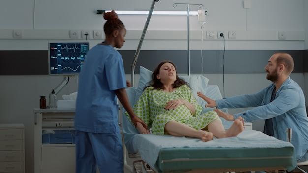 Junge frau mit schwangerschaft, die in der krankenstation wehen bekommt. gestresster ehemann, der eine afroamerikanische krankenschwester für medizinische hilfe und unterstützung gegen schmerzhafte kontraktionen in die klinik bringt