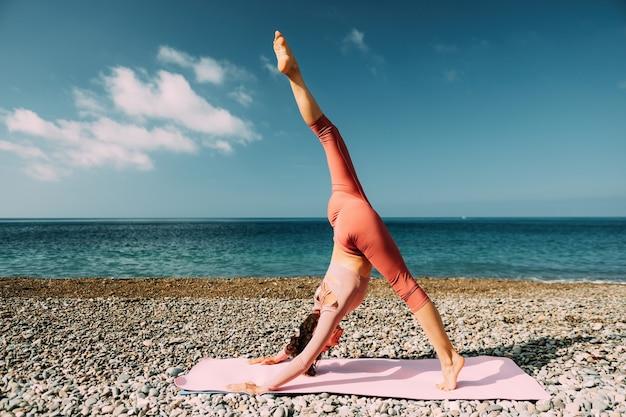 Junge frau mit schwarzem haar fitnesstrainer in leggings und tops macht stretching und pilates an