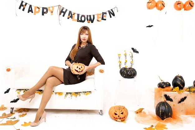 Junge frau mit schwarzem kürbis in halloween-dekoration