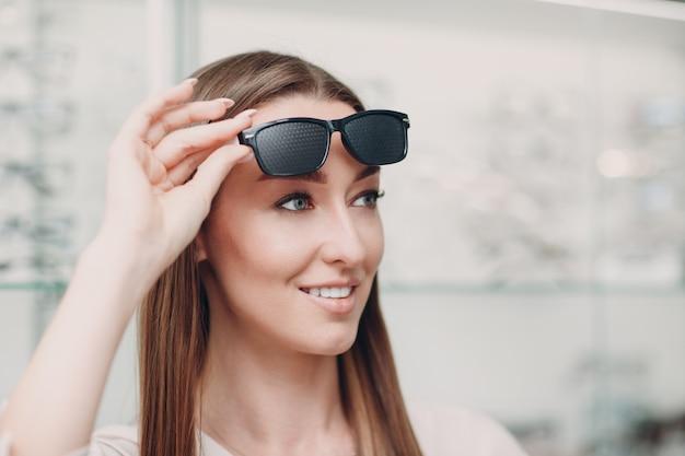 Junge frau mit schwarzen gelochten brillen für das sehtraining. trainer für perforierte brillen.
