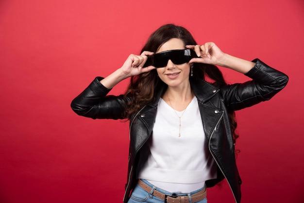 Junge frau mit schwarzer brille auf rotem grund. foto in hoher qualität