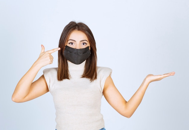 Junge frau mit schwarzer medizinischer maske, die auf ihren kopf zeigt.