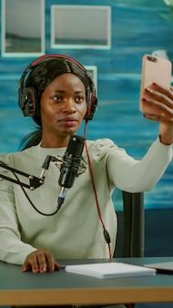 Junge frau mit smartphone, die selfie in der aufnahmeepisode des unterhaltungsgeschäfts macht