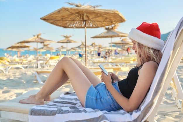 Junge frau mit smartphone im hut von santa claus ruht am strand in der sonnenliege sitzen. weihnachts- und neujahrsferien, ferien, reisen, tourismuskonzept