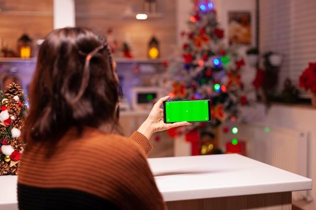 Junge frau mit smartphone mit grünem bildschirm
