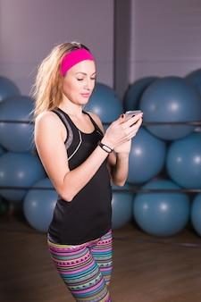 Junge frau mit smartphone und fitness-tracker im fitnessstudio, trainingspause