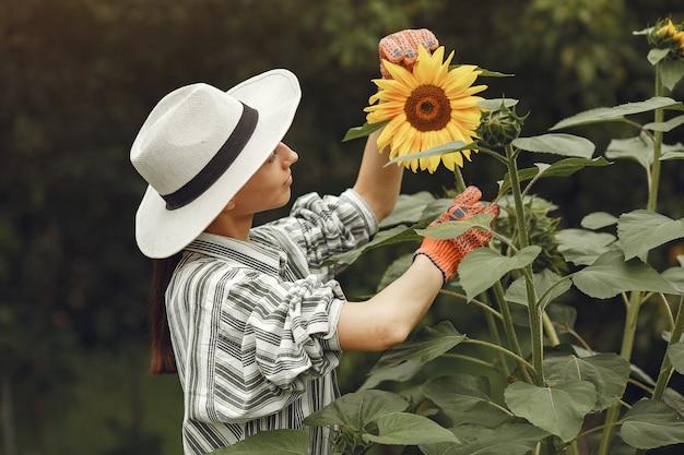 Junge frau mit sonnenblumen. dame mit hut. mädchen in einem garten.