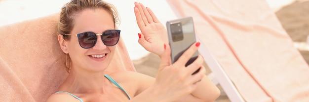 Junge frau mit sonnenbrille, die auf der strandliege liegt und auf dem bildschirm des mobiltelefons winkt