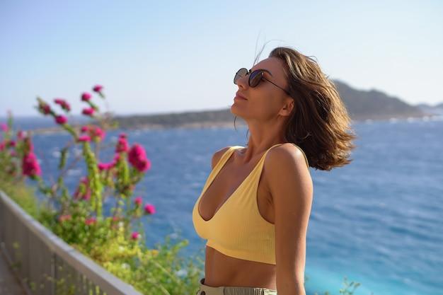 Junge frau mit sonnenbrille gut gelaunt im urlaub am strand einen heißen sommertag genießen