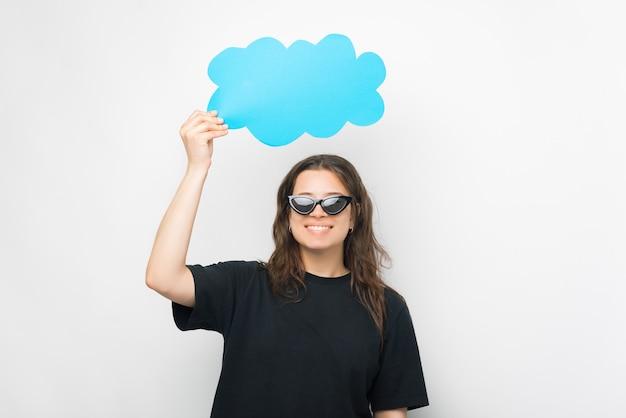 Junge frau mit sonnenbrille hält eine papierwolke über ihrem kopf.