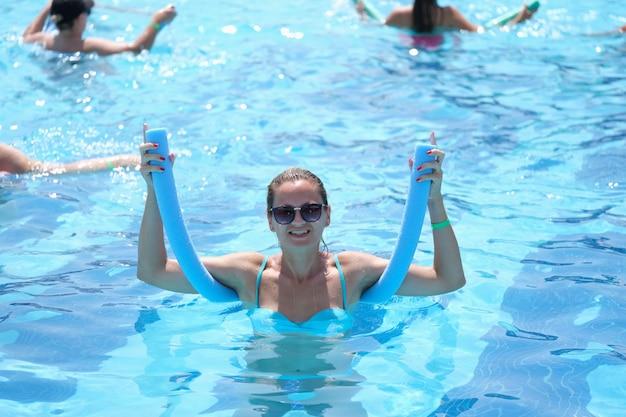 Junge frau mit sonnenbrille hält nudel für aqua-aerobic im schwimmbad