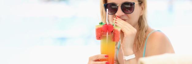 Junge frau mit sonnenbrille trinkt bunten alkoholischen cocktail am strand
