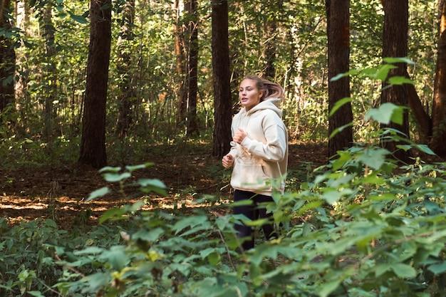 Junge frau mit sport-hoodie, die im park läuft, gesundes lebensstil- und wellnesskonzept