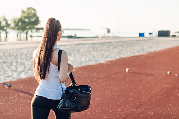 Junge frau mit sporttasche geht auf sportplatz
