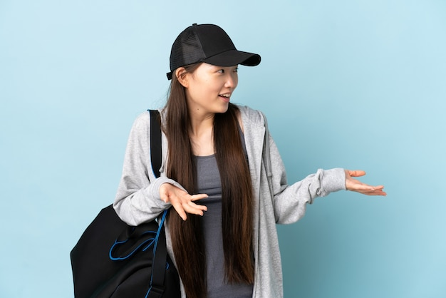 Junge frau mit sporttasche über isoliertem blau mit überraschungsausdruck beim betrachten der seite