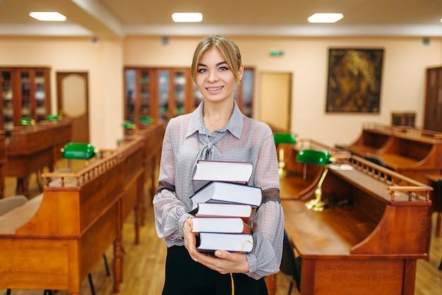 Junge frau mit stapel bücher im lesesaal, universitätsbibliothek. weibliche person im wissensdepot
