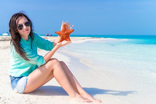 Junge frau mit starfish auf weißem strand im naturreservat