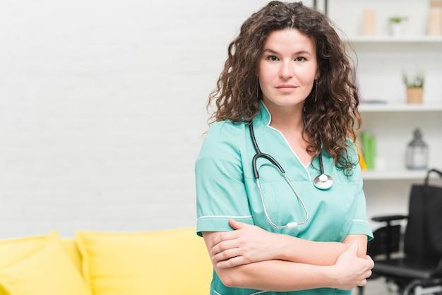 Junge frau mit stethoskop um ihren hals, der im krankenhaus steht