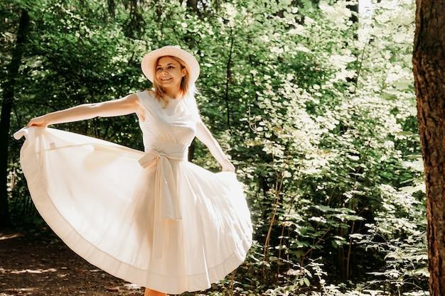 Junge frau mit strohhut, die den saum ihres weißen kleides hält