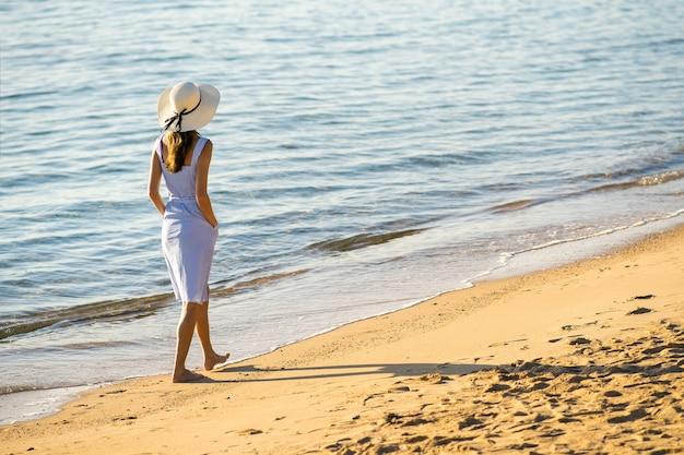 Junge frau mit strohhut und einem kleid, die allein am leeren sandstrand am meer spazieren geht. einsames touristisches mädchen, das auf urlaubsreise den horizont über der ruhigen meeresoberfläche betrachtet.