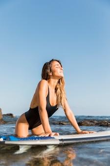 Junge frau mit surfbrett wetter genießen