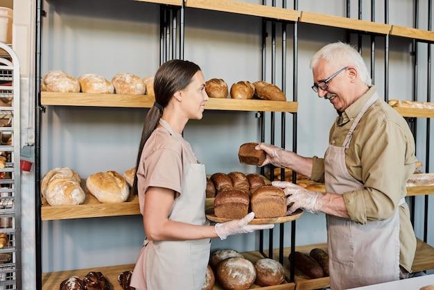 Junge frau mit tablett brot, während sie ihrem vater beim bäckereigeschäft hilft