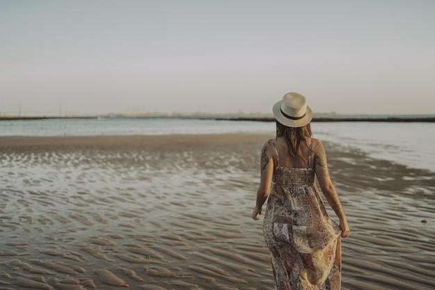 Junge frau mit tätowierungen, die ein kleid und einen strohhut auf verschwommenem ozean trägt