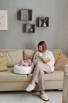 Junge frau mit tasse tee und buch sitzt auf der couch von ihrer kleinen tochter