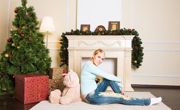 Junge frau mit teddybär nahe kamin im weihnachtlich geschmückten hausinneren