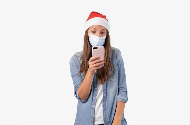 Junge frau mit telefon, medizinischer maske und weihnachtsmütze. weihnachtseinkäufe online in quarantäne.