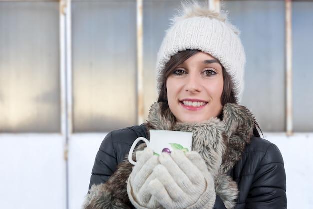Junge frau mit trinkender tasse tee der winterkappe