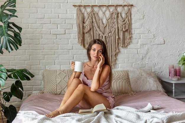 Junge frau mit überraschtem gesicht im rosa pyjama unter verwendung des smartphones beim sitzen auf dem bett zu hause. mit freunden chatten. entspannen und eine tasse heißen kaffee oder tee trinken.