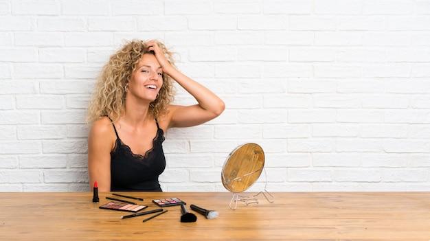 Junge frau mit vielen make-upbürste in einem tabellenlachen