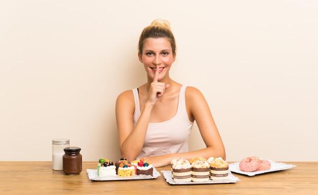 Junge frau mit vielen verschiedenen minikuchen in einer tabelle, die ruhegeste tut
