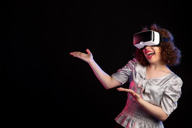 Junge frau mit virtual-reality-headset bei dunklen visuellen tech-vision-spielen