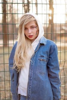 Junge frau mit vorübergehend gemalten blumen auf dem gesicht. teenager-mädchen mit langen blonden haaren tragen jeansjacke und kapuzenpulli