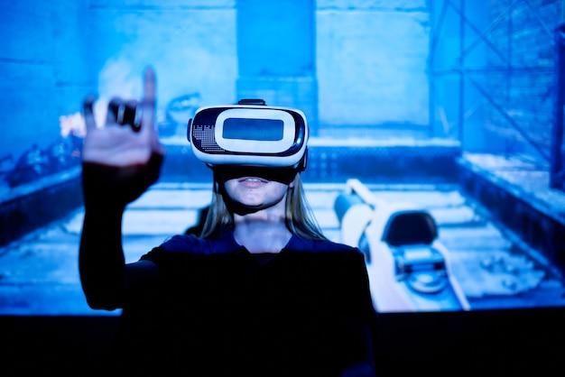 Junge frau mit vr brille, die virtuellen knopf drückt, während sie gegen große leinwand mit projektion des neuen e-sport-videospiels steht