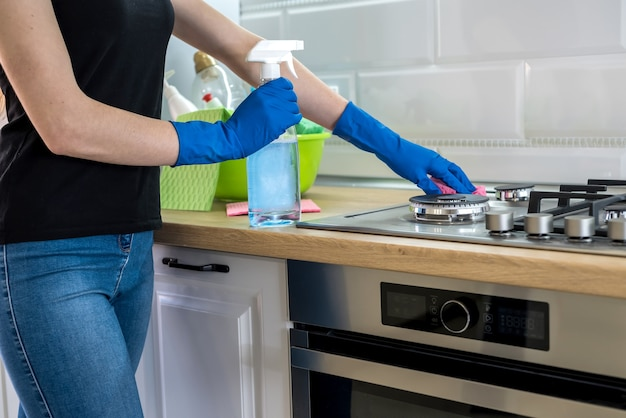 Junge frau mit waschflüssigkeit und lappen wäscht und putzt in der küche