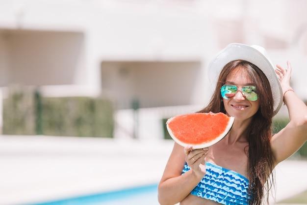 Junge frau mit wassermelone, die draußen im sommerurlaub entspannt