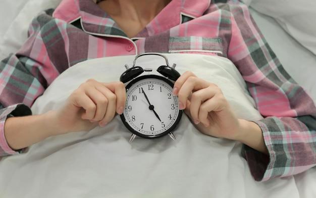 Junge frau mit wecker zu hause im bett liegend. konzept der schlafstörung